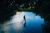 A man and his son paddle board along a jungle river in the interior of Guam.