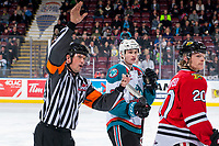 KELOWNA, CANADA - MARCH 3: Kaedan Korczak #6 of the Kelowna Rockets and Joachim Blichfeld #20 of the Portland Winterhawks stand on the ice as referee Tyler Adair calls to the bench for the return of players on March 3, 2019 at Prospera Place in Kelowna, British Columbia, Canada.  (Photo by Marissa Baecker/Shoot the Breeze)