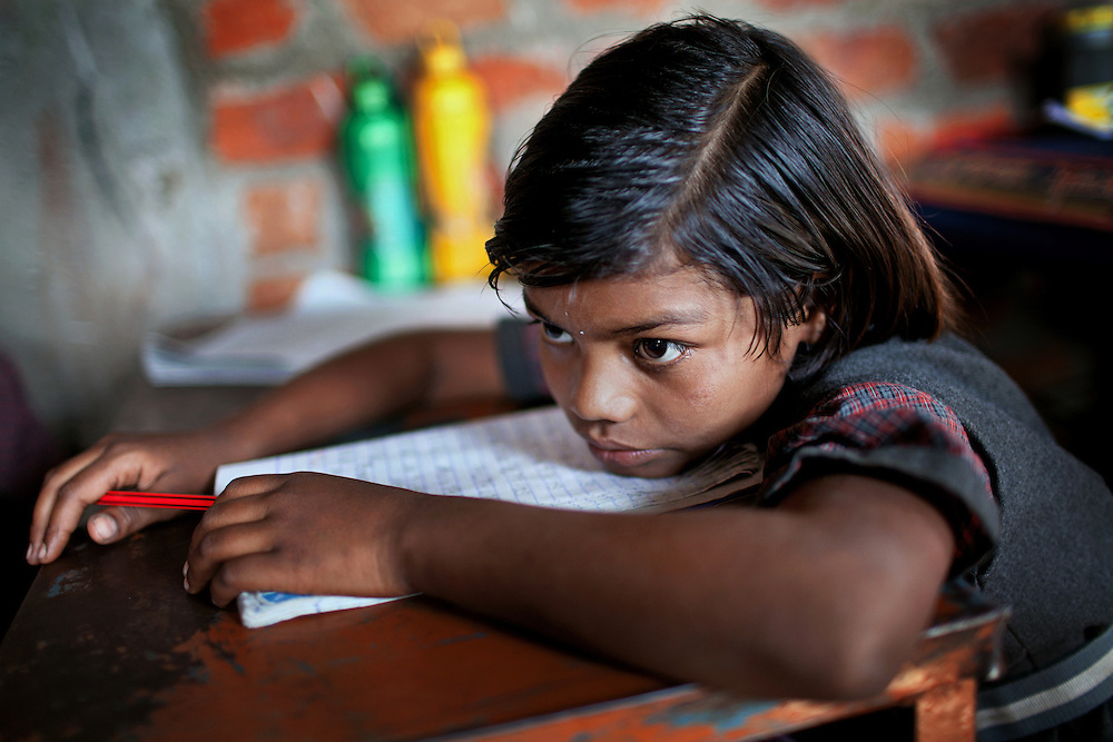 During lesson, Poonam, 9, is leaning on her desk inside the cozy, private school she regularly attends with her sister Jyoti, 10, since 2011, and located by their newly built home in Oriya Basti, one of the water-contaminated colonies in Bhopal, central India, near the abandoned Union Carbide (now DOW Chemical) industrial complex, site of the infamous '1984 Gas Disaster'.