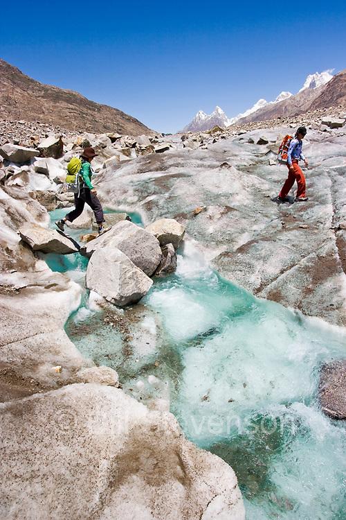 Two women crossing a stream on the Biafo glacier in the Karakoram Himalaya in Pakistan