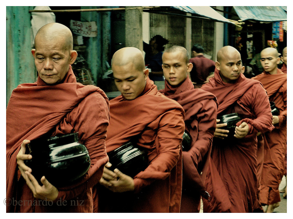 A long line of Burmese monks walks in the streets of Rangoon, the capital of Burma, in a daily round to collect food and bless the people, days after the massive protest of the monks through the streets of the cities. Friday, October 5, 2007. Rangoon, Myanmar (Burma).