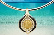 Commercial advertising photo of a spectacular pendant consisting of a gold coin, inlaid with diamonds and black coral in gold frame.