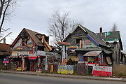 """The Heidelberg Project: Bringing Colour, Art, and Controversy to a Decaying Part of Detroit<br /> <br /> Watching the deterioration of his impoverished, crime-riddenneighborhood of McDougall-Hall two decades after Detroit's 1967 race riots, artist Tyree Guyton felt the need to do something. So he picked up a paintbrush and painted pastel polka dots all over his grandfather's Heidelberg Street house.<br /> Guyton's paint job was the first act toward what became the Heidelberg Project, an outdoor community art project aimed at breathing life back into his decaying district. Encouraged by his grandfather, and with the help of local kids, Guyton began decorating the abandoned homes beside the polka-dot house and installing art made from salvaged materials.<br /> The project now spans two blocks and is constantly evolving, anchored by the altered houses. One ramshackle two-story home is covered in stuffed animals. Another is painted with numbers of wildly varying sizes and colors. Strewn across the yards are sculptures incorporating decorated cars, shopping carts, doors, shoes, and household appliances.<br /> Though the infusion of color and creativity has attracted a stream of appreciative visitors to McDougall-Hall, the Heidelberg Project has some vocal critics. Chief among them is the city of Detroit, which demolished parts of the community in 1991 and 1999.<br /> Local detractors view the Heidelberg Project as an eyesore and health hazard, and resent the fact that it draws further attention to Detroit's urban blight. On November 12 of this year, the project's """"House of Soul,"""" an abandoned house decorated with hundreds of records, burned to the ground in a suspected arson attack. This followed a suspicious fire in May, in which an art-enhanced building called the """"Obstruction of Justice House"""" was destroyed.<br /> Undeterred, Guyton has responded to the destruction with relentless optimism and vowed to continue expanding his vibrant art community.<br /> <br /> *Visit """