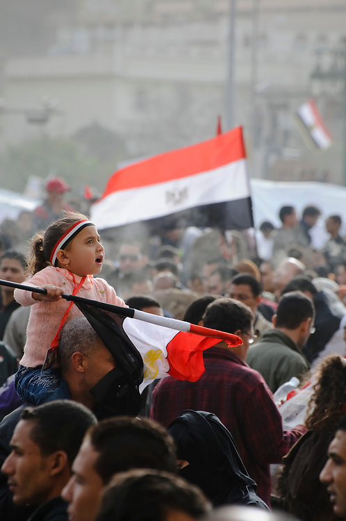 An Egyptian girl, sitting atop the shoulders of her father, takes in the events around her with a look of wonder on her face. She is at a rally in Tahrir Square, two weeks after the resignation of President Hosni Mubarak. (Cairo, Egypt - February 25, 2011)