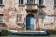 A boat moors to an old weathered building with blue door in Venice. Venezia, founded in the 400s AD, is capital of Italy's Veneto region, named for the ancient Veneti people from the 900s BC. The romantic City of Canals stretches across 100+ small islands in the marshy Venetian Lagoon along the Adriatic Sea, between the mouths of the Po and Piave Rivers. The Republic of Venice was a major maritime power during the Middle Ages and Renaissance, a staging area for the Crusades, and a major center of art and commerce (silk, grain and spice trade) from the 1200s to 1600s. The wealthy legacy of Venice stands today in a rich architecture combining Gothic, Byzantine, and Arab styles. Venice and the Venetian Lagoon are honored on UNESCO's World Heritage List.