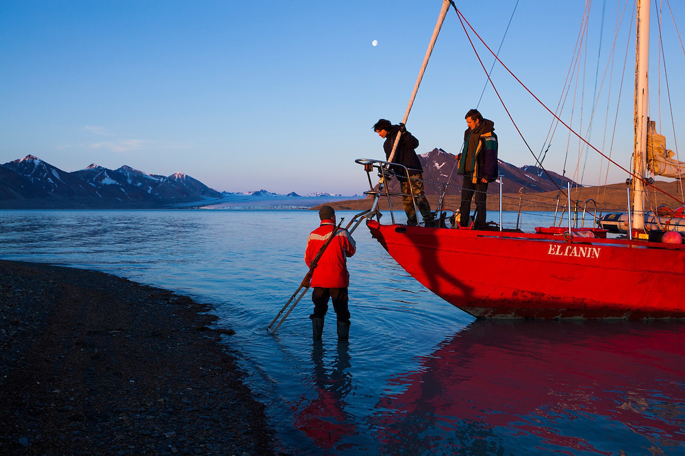 Marcin Tukalski, student at the University of Silesia, climbs off the Eltanin, anchored in Josephbukta, to visit a research outpost in Calypsobyen, Svalbard. The yacht travels from Poland to Svalbard every summer to provide transportation to researchers and tourists. Recherchebreen is visible in the distance.