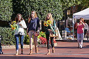Young woman carry sunflowers from the Farmers Market along Main Street in downtown Greenville, South Carolina.