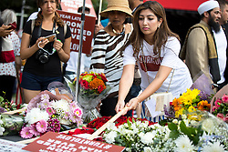 © Licensed to London News Pictures. 03/06/2018. London, UK. Members of the public lay flowers to mark one year since the London Bridge and Borough Market terror attacks. A series of events have taken place throughout the day, including a service of commemoration at Southwark Cathedral, the planting of an olive tree in the Cathedral grounds, a minute's silence at 4:30pm and the laying of flowers.  Photo credit : Tom Nicholson/LNP