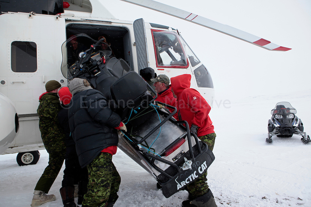 Canadian Rangers load a snowmobile with a broken track suspension inside a S-61 helicopter in Baring Bay on Devon Island, Nunavut, during Nunalivut 2012 sovereignty exercise by Canadian Forces in arctic Canada. April 2012.