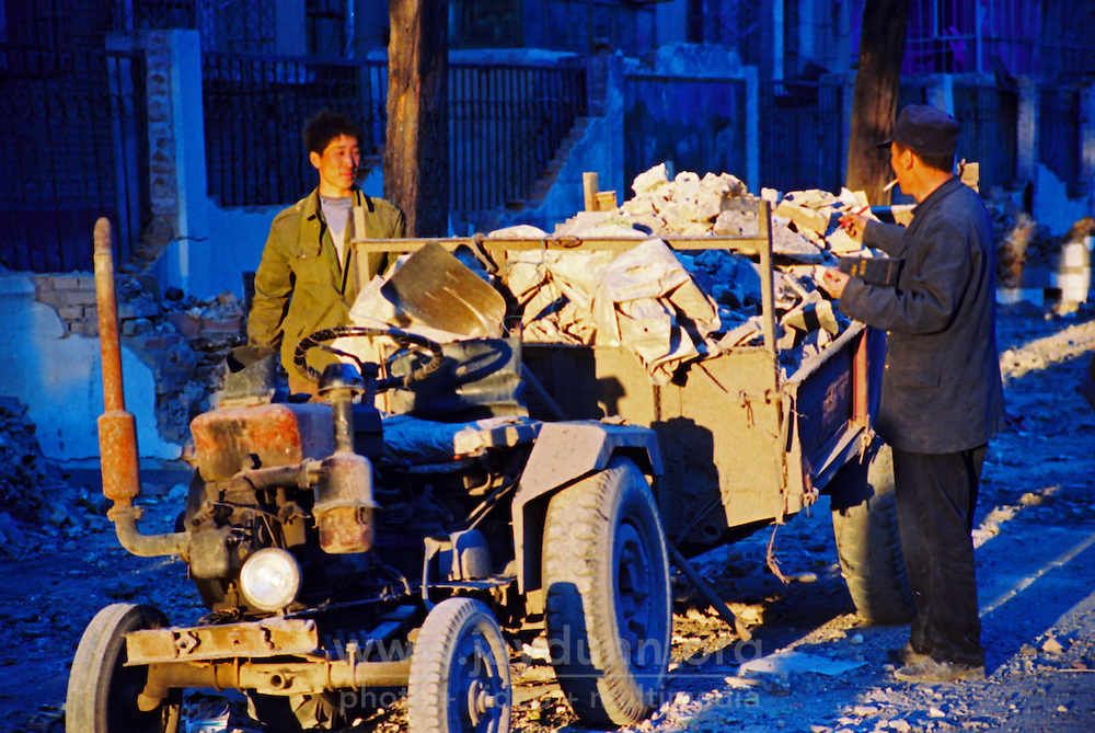 China, Datong, 2007. Most small-scale demolition work is done by sledgehammer. This team is packing up at last light in the industrial city of Datong..