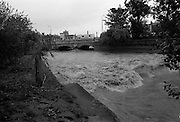"Flooding at the Dodder..1986..26.08.1986..08.26.1986..28th August 1986..As a result of Hurricane Charly (Charlie) heavy overnight rainfall was the cause of severe flooding in the Donnybrook/Ballsbridge areas of Dublin. In a period of just 12 hours it was stated that 8 inches of rain had fallen. The Dodder,long regarded as a ""Flashy"" river, burst its banks and caused great hardship to families in the 300 or so homes which were flooded. Council workers and the Fire Brigades did their best to try and alleviate some of the problems by removing debris and pumping out some of the homes affected..Note: ""Flashy"" is a term given to a river which is prone to flooding as a result of heavy or sustained rainfall...Image shows the torrent going over the weir just before the road bridge in Ballsbridge,Dublin."