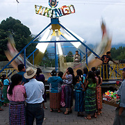 "Girls wait anxiously in line for a turn on the ""Vikingo"" ride during a celebration in San Pedro la Laguna.  People from all other cities surrounding Lago de Atitlan gather for celebrations, each group wearing unique clothing designs and styles to identify their culture.  San Pedro la Laguna, Lago de Atitlan, Guatemala, June 2009.  (Photo/William Byrne Drumm)"