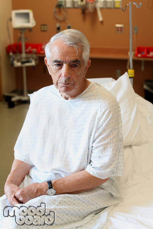 Elderly man sitting on hospital bed