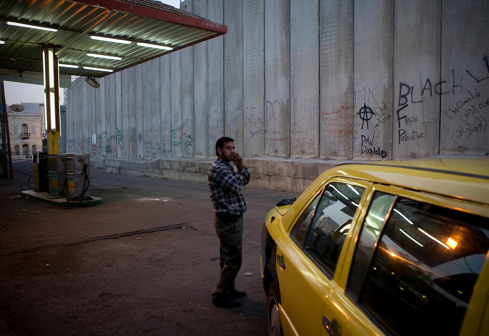 A Palestinian man talks on the phone next to his taxi under the shadow of a section of the security wall, Bethlehem. 14th May 2008