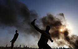 June 9, 2017 - Gaza City, Gaza Strip, Palestinian Territory - A Palestinian protester uses a slingshot to hurl stones towards Israeli security forces during clashes following a demonstration against the blockade on the Gaza Strip, near the border fence east of Jabalia refugee camp.  (Credit Image: © Yasser Qudih/APA Images via ZUMA Wire)