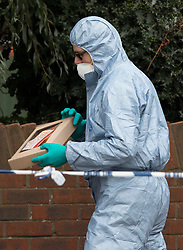 © Licensed to London News Pictures. 08/10/2016. London, UK. A forensics officer places a fast food packet in an evidence box at the scene of a shooting in Eastney Road, Croydon. Police were called to reports of a man suffering a gunshot wound at 11.30 PM on Friday night. Officers from the Homicide and Major Crime Command are investigating after the man was pronounced dead at the scene.Photo credit: Peter Macdiarmid/LNP
