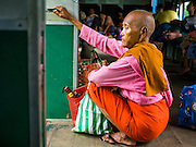 26 OCTOBER 2015 - YANGON, MYANMAR:  A Burmese nun sits in the doorway of the Yangon Circular Train. The Yangon Circular Railway is the local commuter rail network that serves the Yangon metropolitan area. Operated by Myanmar Railways, the 45.9-kilometre (28.5 mi) 39-station loop system connects satellite towns and suburban areas to the city. The railway has about 200 coaches, runs 20 times daily and sells 100,000 to 150,000 tickets daily. The loop, which takes about three hours to complete, is a popular for tourists to see a cross section of life in Yangon. The trains run from 3:45 am to 10:15 pm daily. The cost of a ticket for a distance of 15 miles is ten kyats (~nine US cents), and for over 15 miles is twenty kyats (~18 US cents).     PHOTO BY JACK KURTZ