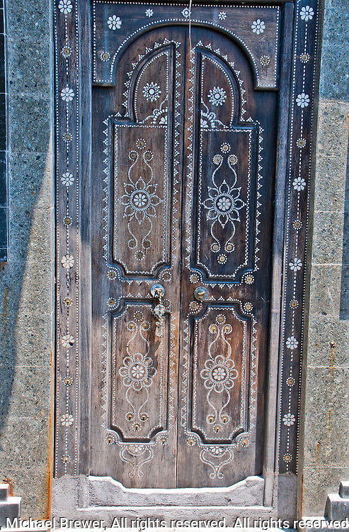 Old ornate carved wooden door at Amlapura Palace in Eastern Bali, Indonesia