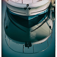 Pleasure boats reflection in water at Brighton Marina, in East Sussex, England.