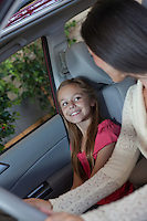 Daughter sitting in car with her mother