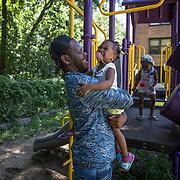 WASHINGTON, DC -JUL22: Erik Beard, 23,  who works at Beautiful U summer camp in Southeast, Washington, DC, through DC's Student Youth Employment Program, SYEP, helps Jah'Arah Edwards, 2, climb the monkey bars, July 22, 2015. (Photo by Evelyn Hockstein/For The Washington Post)