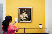 "FLORENCE, ITALY - 29 JUNE 2016: A visitor photographs the ""Bacchus"" (1595) by Caravaggio at the Uffizi Gallery in Florence, Italy, on June 29th 2016.<br /> <br /> Art historian Eike Schmidt, former curator and head of the Department of Sculpture, Applied Art and Textiles at the Minneapolis Institute of Arts, became the first non-Italian director of the Uffizi in August 2015, replacing Antonio Natali who directed the gallery for 9 years. One of the main goals of the new director is to open the Vasari Corridor to the general public. Currently the corridor can only be visited with group reservations made by external tour and travel agencies throughout the year.<br /> <br /> The Vasari Corridor is is a 1-kilometer-long (more than half mile) elevated enclosed passageway which connects the Palazzo Vecchio with the Palazzo Pitti, passing through the Uffizi Gallery and crossing the Ponte Vecchio above the Arno River, in Florence. The passageway was designed and built in 1564 by Giorgio Vasari in only 6 months to allow Cosimo de' Medici and other Florentine elite to walk safely through the city, from the seat of power in Palazzo Vecchio to their private residence, Palazzo Pitti. The passageway contains over 1000 paintings, dating from the 17th and 18th centuries, including the largest and very important collection of self-portraits by some of the most famous masters of painting from the 16th to the 20th century, including Filippo Lippi, Rembrandt, Velazquez, Delacroix and Ensor."