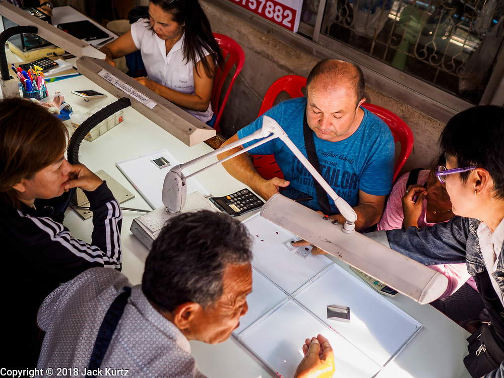 22 DECEMBER 2018 - CHANTABURI, THAILAND: A European gem buyer (center, background) looks at gems brought to him in the gem market in Chantaburi. The gem market in Chantaburi, a provincial town in eastern Thailand, is open on weekends. Chantaburi used to be an active gem mining area in Thailand, but the mines are played out now. Now buyers and sellers come from around the world to Chantaburi for the weekend market. Many of the stones come from Myanmar, others come from mines in Afghanistan and Africa.     PHOTO BY JACK KURTZ