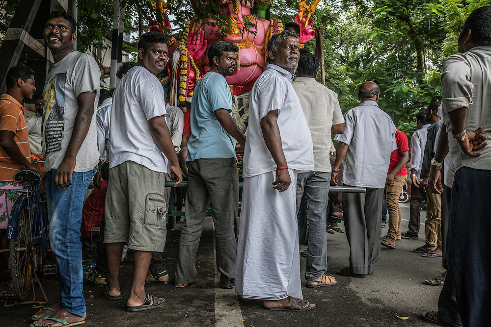 Men from central Pondicherry navigate their large statue of the Lord Ganesha under low branches and electric wires on their way to the fishing port to put in on a boat and carry it out to sea to dump it into the Bay of Bengal, symbolically return it to nature.  Pondicherry, India.