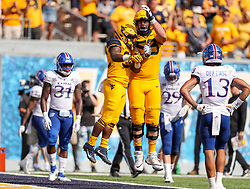 Oct 6, 2018; Morgantown, WV, USA; West Virginia Mountaineers running back Martell Pettaway (32) celebrates with West Virginia Mountaineers offensive lineman Colton McKivitz (53) after scoring a touchdown during the third quarter against the Kansas Jayhawks at Mountaineer Field at Milan Puskar Stadium. Mandatory Credit: Ben Queen-USA TODAY Sports