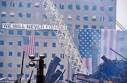 "22 SEPTEMBER 2011 - NEW YORK, NY: American flags and a banner hang from a building in the wreckage of the World Trade Center complex at ""Ground Zero"" of the WTC terrorist attack, while recovery work continues Sept. 22, 2001.  More than 2,900 people were killed when terrorists crashed two airliners into the towers on Sept. 11, 2001.  PHOTO BY JACK KURTZ"