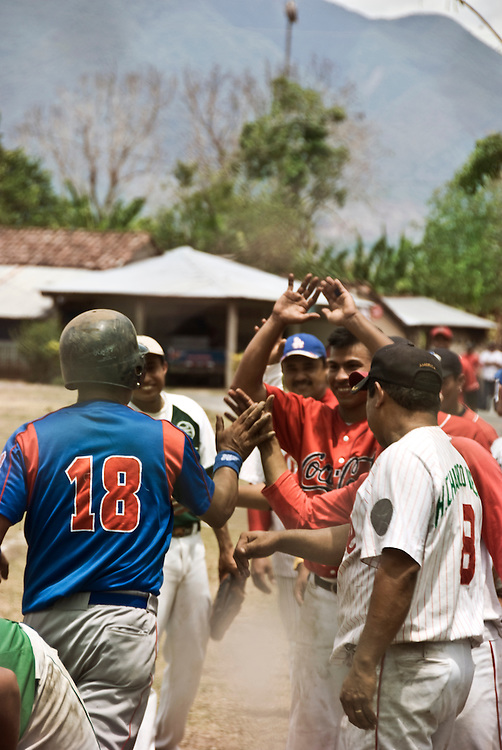 Players celebrating a grand slam in a friendly match of a local baseball league on Ometepe Island in the middle of Lake Cocibolca, Nicaragua. Baseball is the national sport of Nicaragua. The players and fans are extremely passionate even in these rural leagues playing on dirt fields with antiquated equipment.