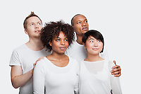 Young multi-ethnic friends in white t-shirts looking away over white background