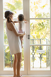 Mother Holding Baby Daughter by French Door