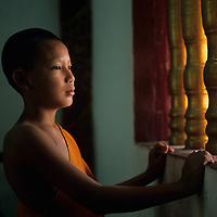 Asia, Laos, Luang Prabang, Young Buddhist Novice peers through window at Wat Sop Temple in early morning