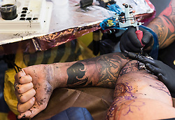 © Licensed to London News Pictures. 23/09/2016. Visitors have their tattoos done by a tattoist at the 12th International LOndon Tattoo Convention, London, UK. Photo credit: Ray Tang/LNP