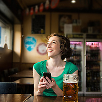 Young woman laughing while holding her smartphone inside a pub.