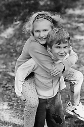 boy giving a girl a piggy back ride