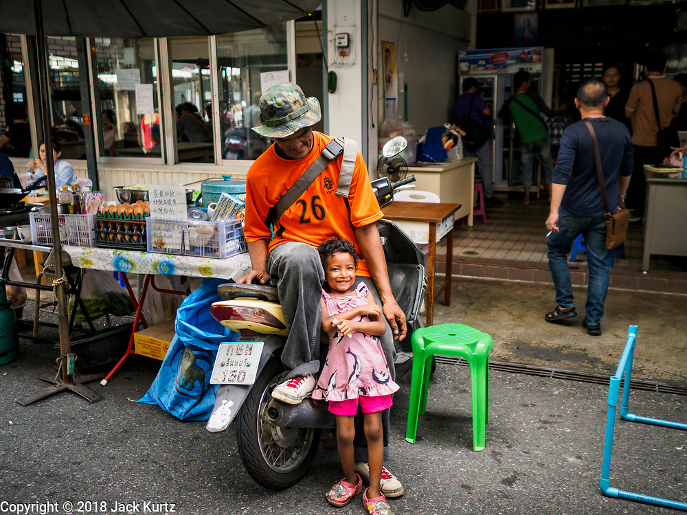 22 DECEMBER 2018 - CHANTABURI, THAILAND: A Thai man selling loose gems waits for customers with his daughter in the gem market in Chantaburi. The gem market in Chantaburi, a provincial town in eastern Thailand, is open on weekends. Chantaburi used to be an active gem mining area in Thailand, but the mines are played out now. Now buyers and sellers come from around the world to Chantaburi for the weekend market. Many of the stones come from Myanmar, others come from mines in Afghanistan and Africa.       PHOTO BY JACK KURTZ