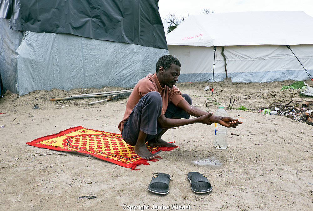 Sudanese man washing his feet befor praying in  The Calais Jungle Refugee and Migrant Camp in France