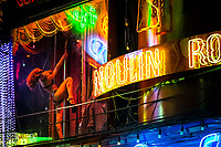 A pole dancer spins in a window of a go-go bar along Walking Street in Pattaya, Thailand.