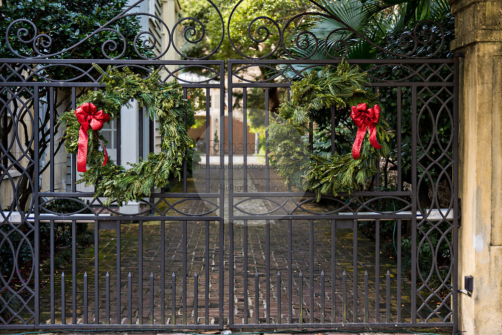 The wrought iron gate of a historic home decorated with Christmas wreaths on the Battery in Charleston, SC.