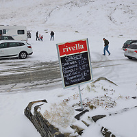 Tourists in snow at the summit of the Oberalp pass  (2044m) linking Uri and Graubunden Cantons in the Swiss Alps, shortly before the road link closes for months. The source of the Rhine is close by.<br /> The area belonged to the National Redoubt, the final Swiss line of defence in the high alps, and is checkered with the remains of millitray installations, many of them underground, still camouflaged.
