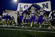 The Logan football team breaks through their velcro banner moments before the game.