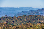 At Bunches Bald Overlook (Milepost 459.5, elevation 4925 feet) on the Blue Ridge Parkway, view the Blue Ridge Mountains (a subset of the Appalachian Mountains), in North Carolina, USA. Admire some of the best views on the Parkway between Cherokee and Balsam Gap, with fall foliage colors in mid October. The scenic 469-mile Blue Ridge Parkway was built 1935-1987 to aesthetically connect Shenandoah National Park (in Virginia) with Great Smoky Mountains National Park in North Carolina, following crestlines and the Appalachian Trail. Local trees release hydrocarbons into the atmosphere and create a characteristic blue haze on pristine days as seen in this photo; but more often a white or gray haze obscures distant views due to air pollution.