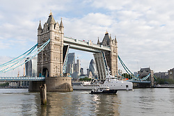 © Licensed to London News Pictures. 18/05/2017. LONDON, UK.  The Game Changer, a newly built superyacht support vessel leaves London under Tower Bridge on the River Thames after her first visit to the capital. The 70-meter superyacht support vessel has a large helideck so that yacht owners can take larger helicopters on long range flights to their mother yachts and 250 square metres of open deck space for tenders and toys, plus offices, facilities and accommodation for 22 crew and staff below deck. Built by Dutch Shipbuilder, Damen, the Game Changer was launched in March this year and recently completed sea trials in the North Sea. Photo credit: Vickie Flores/LNP