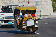HAVANA, CUBA - OCTOBER 21, 2006: Unidentified tourists enjoy trip by the motorbike taxi, known as Coco taxi, at Malecon avenue in Havana, Cuba.