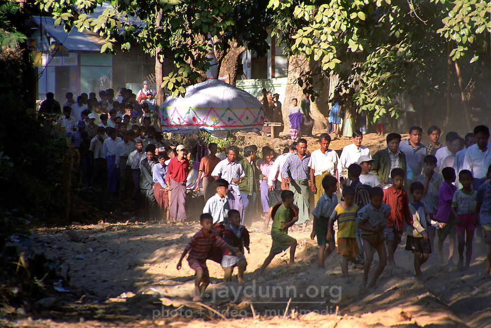 BURMA (MYANMAR), Mandalay Division, Myinkabar. 2006. Aung Thein Thay?s coffin is carried through Myinkabar, accompanied by a heavy triangular bell, and a priest scattering coins and paper wishes.
