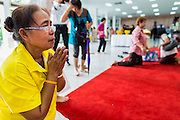 09 OCTOBER 2014 - BANGKOK, THAILAND:  A woman prays for Bhumibol Adulyadej, the King of Thailand in the lobby of Siriraj Hospital. People wear yellow when they pray for the King because it's the King's color. The King has been hospitalized at Siriraj Hospital since Oct. 4 and underwent emergency gall bladder removal surgery Oct. 5. The King is also known as Rama IX, because he is the ninth monarch of the Chakri Dynasty. He has reigned since June 9, 1946 and is the world's longest-serving current head of state and the longest-reigning monarch in Thai history, serving for more than 68 years. He is revered by the Thai people and anytime he goes into the hospital thousands of people come to the hospital to sign get well cards.  PHOTO BY JACK KURTZ