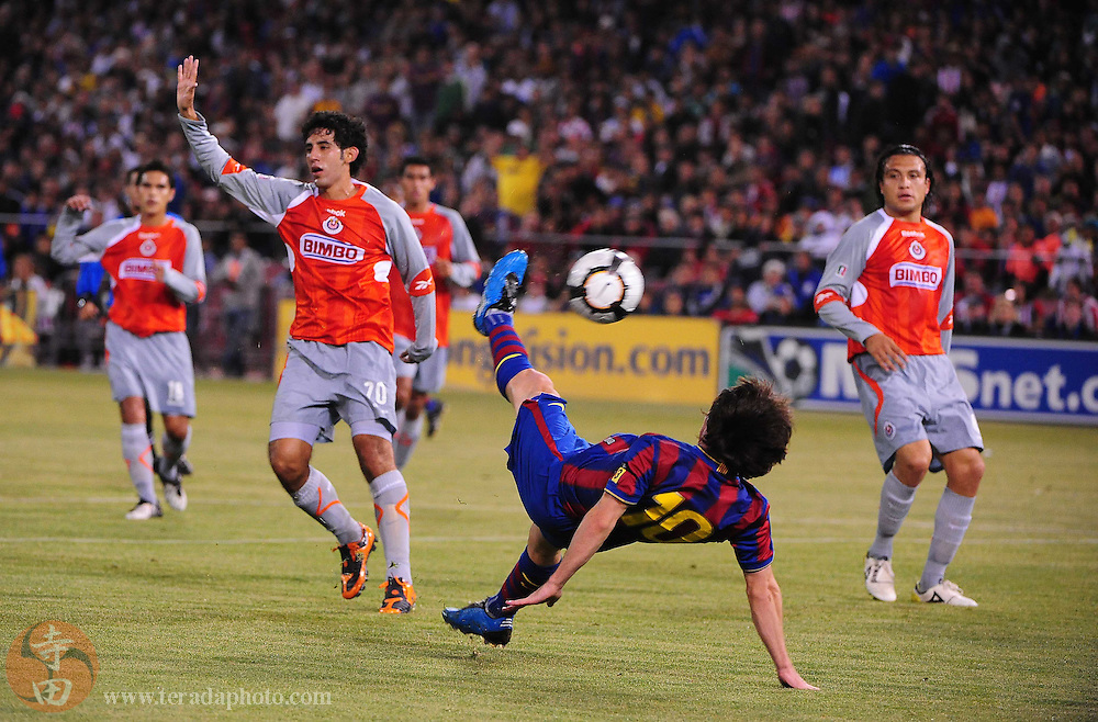 August 8, 2009; San Francisco, CA, USA; FC Barcelona forward Lionel Messi (bottom) kicks in front of Chivas de Guadalajara players after a whistle was blown during the first half in the Night of Champions international friendly contest at Candlestick Park.