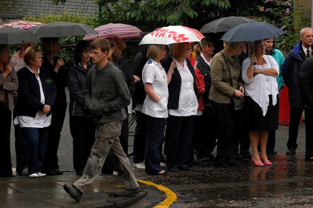 A funeral procession for Lothian and Borders fire fighter Ewan Williamson who was killed helping rescue people for a fire at the Balmoral bar in Edinburgh on 12th July 2009 was held today. The procession left Tollcross Fire Station making it's way to St Giles Cathedral where a private service was held...Picture shows members of the public look on as the procession makes its way to St Giles in Edinburgh.